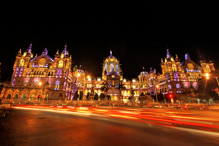 Mumbai's CST (Chatrapati Shivaji Terminus) illuminated at night with vehicular traffic in foreground and copy space.