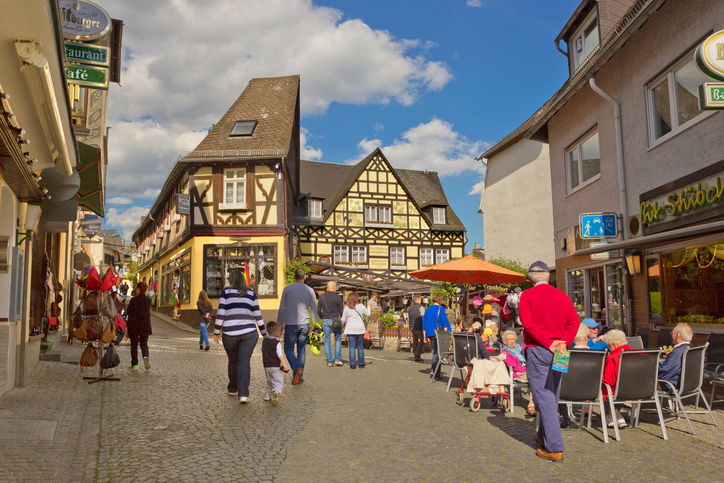Ruedesheim am Rhein, Germany - May 4, 2016: Small square in small town with timbered houses and walking people