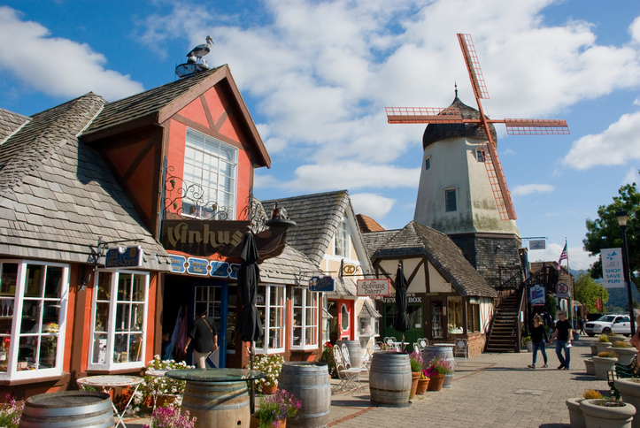 Solvang, USA - May 10, 2016: Street of Solvang, California, in May 2016, with people on the boardwalk, cafes, shops and a windmill in the back