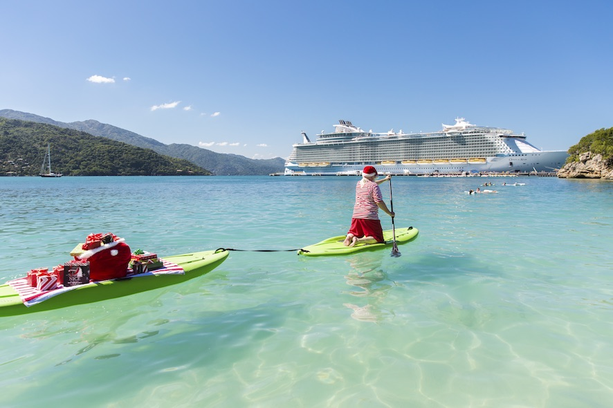 Oasis of the Seas, holiday, rear view of Santa kneeling on paddleboard, paddle board, rowing, towing another board behind with his bag of gifts, presents on a beach towel, paddling toward guests swimming near Oasis of the Seas at Labadee beach, Haiti, fun