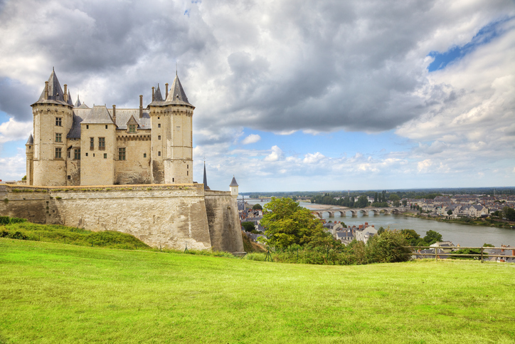"""Saumur, France - July 19, 2009: Panoramic of Saumur Chateau overlooking the Loire river and Valley. Stormy clouds given a nice dramatic look"""