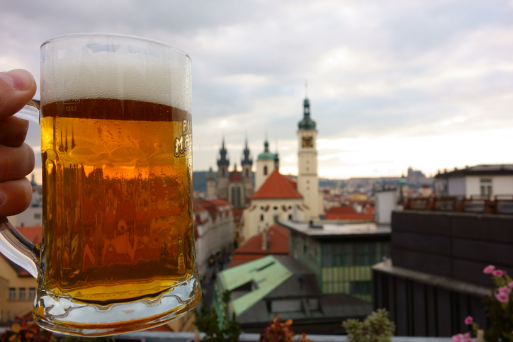 Prague, Czech Republic – October 19, 2015: A fresh pint of Czech craft beer on a rooftop terrace in the center Prague, Czech Republic with many of the Prague landmarks appearing on the background on cloudy mid-October evening in 2015.