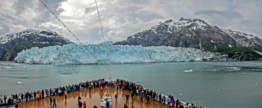 Glacier Bay, Alaska, USA - May 26, 2015:  Passengers on a cruise ship stand on the bow looking at Margerie Glacier