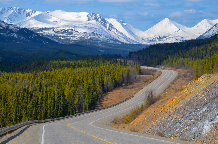 Scenic view of the Alaska Highway in the Yukon, Canada, with snow covered mountains and conifer woods