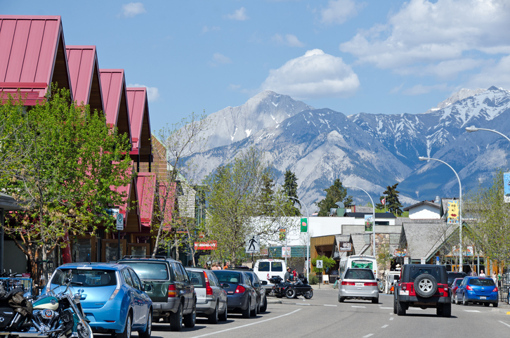 Jasper, Canada - May 27, 2012: The Main Street in the town of Jasper in Jasper National Park , Alberta. It is late spring and early afternoon. This one way street is lined with retail stores and restaurants. The Rocky Mountains are in the background.
