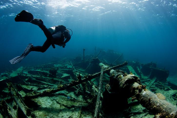 A scuba diver swims over a sunked shipwreck.