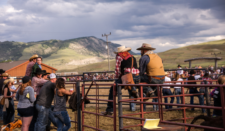 Gardiner, MT, USA - June 20, 2015: The crowd of cowboys and cowgirls line the arena stockade during the annual western rodeo in Gardiner, Montana. The rodeo offers tourists to nearby Yellowstone Park a glimpse into western culture.