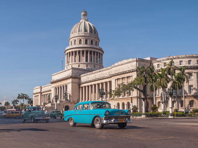 old American cars passing in front of the Capitolio in Havana, Cuba