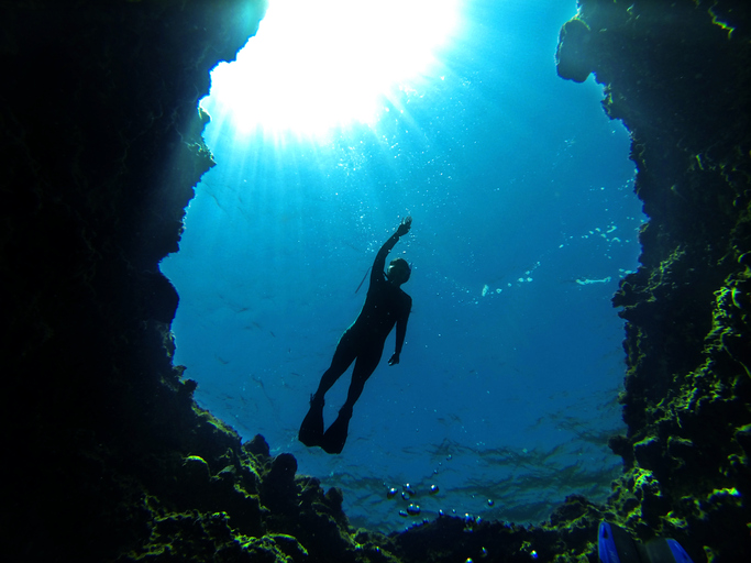 A diver in silhouette over a deep hole in the reef with sunlight streaming.