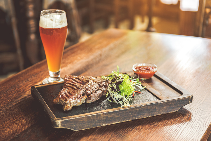 Delicious dish. Close up of fragrant grilled T-bone steak, mix salad and tomato sauce on cutting board with cool lager on wooden table. Pub in the background
