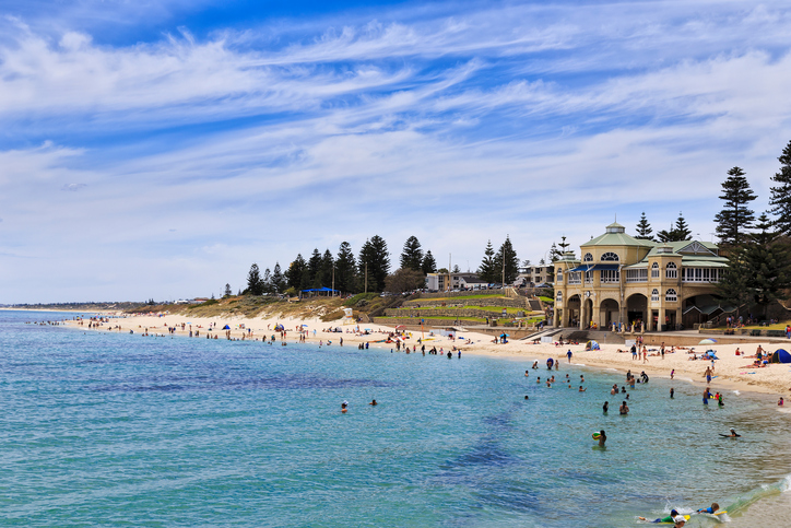 sunny day view of central pavilion building on Cottesloe western beach of Perth with swimming and relaxing people - beachgoers