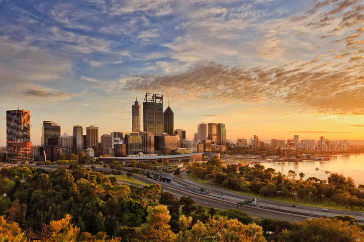 Gold warm sun light litting CBD of Perth city as seen from Kings park with green trees and highway entering the city.