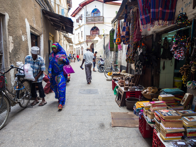 Stone Town, Zanzibar, Tanzania - March 29, 2016: Local people walking on one of the streets in Stone Town, the capital of Zanzibar. Stone Town is famous for its colonial architecture.
