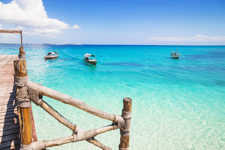 Fishing boast in the sea beside the wooden pier, Zanzibar island
