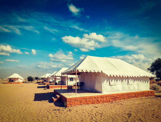 Vintage retro hipster style travel image of luxury tents in desert. Jaisalmer, Rajasthan, India