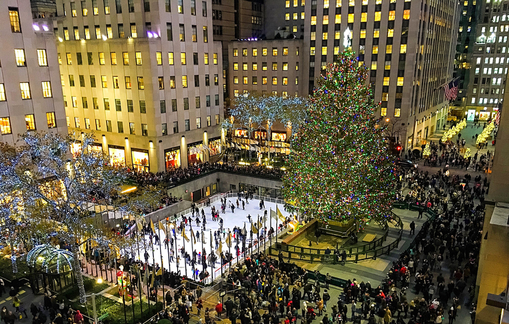 A scenic overview of the hustle and bustle of the holidays at night beneath the magnificent tree in Rockefeller Center.