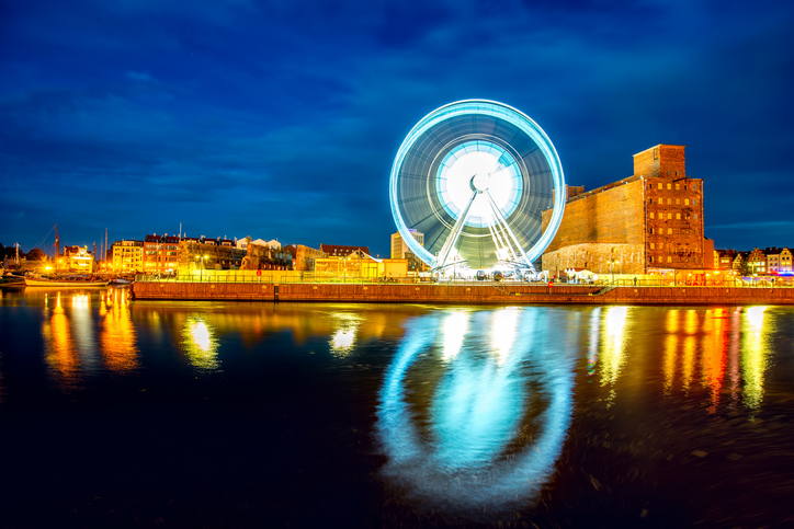 Night view on the riverside with illuminated Ferris wheel in the old city of Gdansk