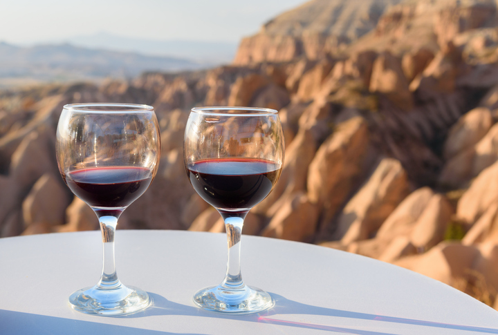 Red Wine glasses on Red valley background in Cappadocia. Nevsehir Province. Turkey