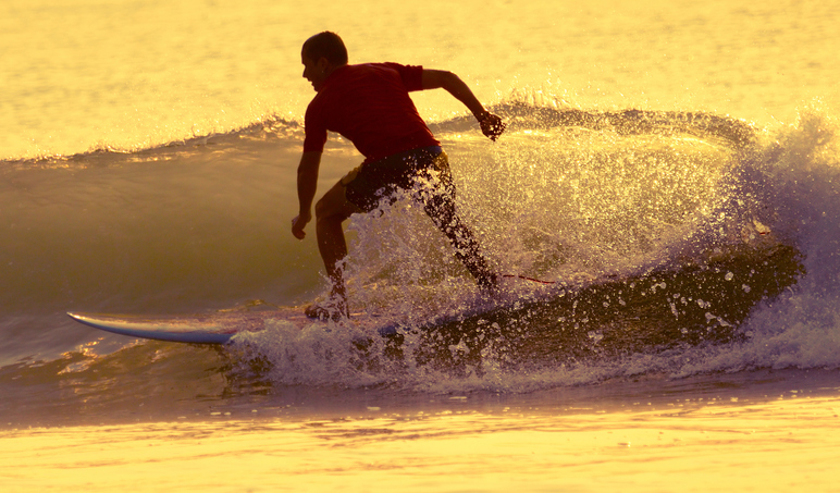 Surfer riding small wave at sunrise