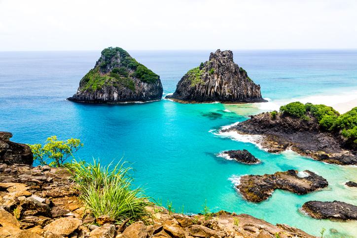 A visão clássica da Ilha Dois Irmãos no arquipélago de Fernando de Noronha com suas cores intensas ressaltadas pelo sol sobre o mar.