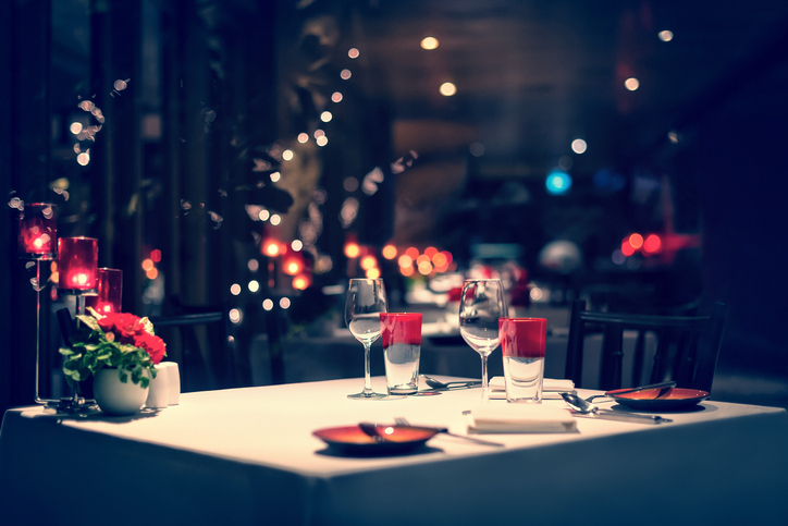 romantic dinner setup, red decoration with candle light in a restaurant. Selective focus. Vintage.