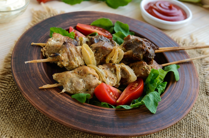 Pieces of meat with onions on skewers (kebab). Serve with sauce, tomatoes and arugula.