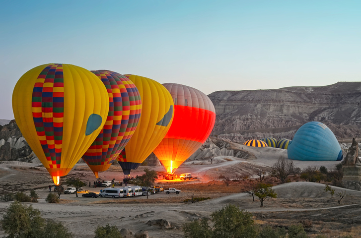 Colorful hot air balloons flying over the valley at Cappadocia, Turkey. Volcanic mountains in Goreme national park