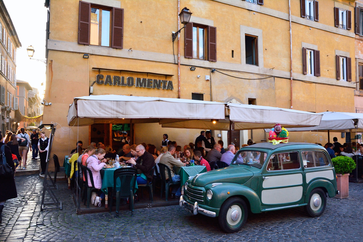 ROME, ITALY - APRIL 10, 2017: People eating traditional italian food in outdoor restaurant Carlo Menta in Trastevere district in Rome, Italy on April 10, 2017.