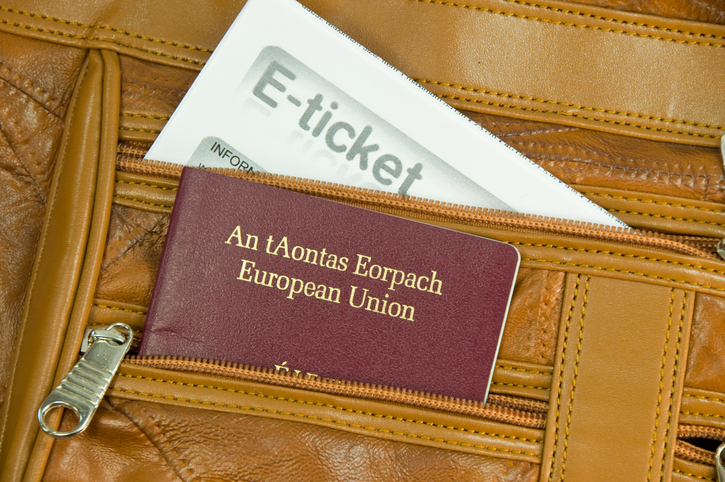 Irish EU Passport and airplane flight E-ticket showing from the pocket of a leather carry-on bag.