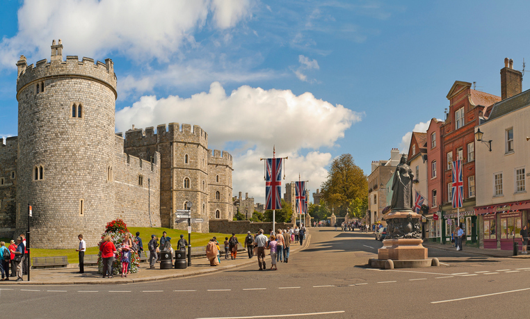 Windsor, United Kingdom - August 28, 2012: View of Windsor Castle, one of the official residences of the British Royal Family and Queen Victoria Statue with people walking and sightseeing