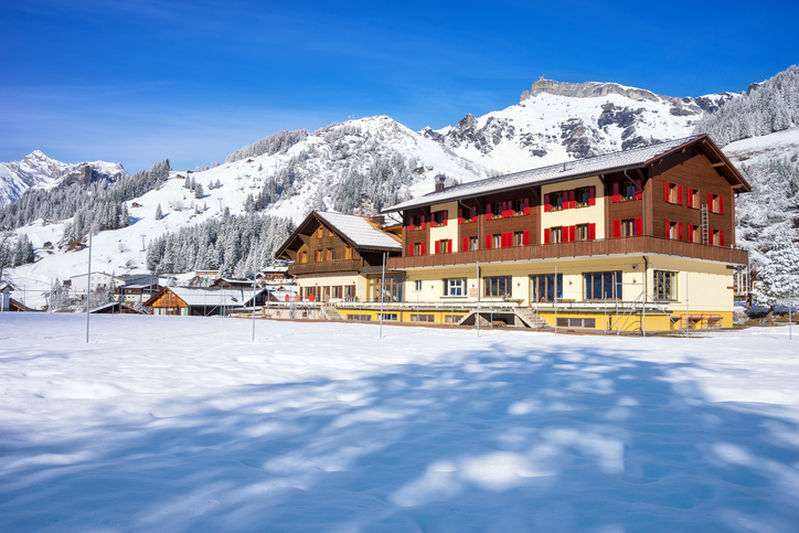Murren, Switzerland - April 10, 2016 : A hotel in a car free mountain village 'Murren' with snow mountain in background.