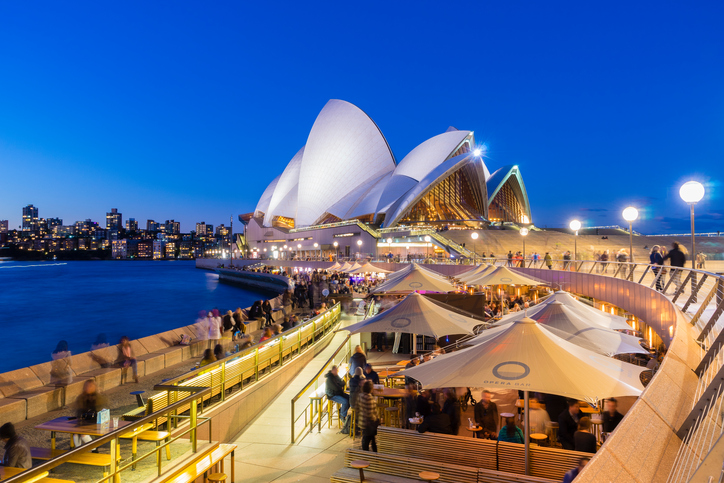 Sydney, Australia - June 25, 2016: View of cafe full of people and the Sydney Opera House at twilight. The cafe offers a stunning view of the Sydney Opera House.