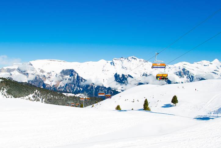 Alpine ski facility in Swiss Alps. Landscape of Switzerland on sunny day. Snow covered Alps mountain peaks. Ski trip in Swiss Alps. Landscape with valley, village and mountains.