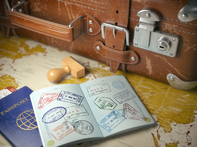 Travel or turism concept.  Old  suitcase  with opened passport with visa stamps. 3d illustration