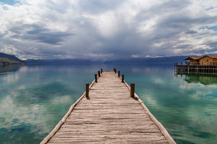 Lake Ohrid with a wooden pier and dramatic sky.