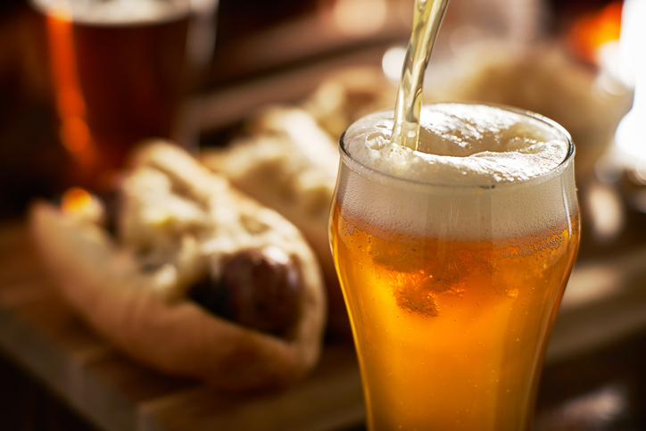 pouring amber beer into mug with bratwursts in background close up
