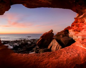 Looking out from a small cave at  Gantheaume Point  Broome  Western Australia at sunset. This is the location of the famous Gantheaume Point Dinosaur footprints but they can only be seen at low tide.