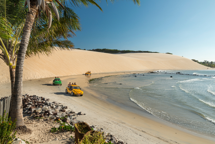 Natal, Rio Grande do Norte, Brazil. 01st September 2017. Three buggy (bugre) driving off-road near the water at the beach of Genipabu (also known as Jenipabu). Local popular trourist attraction, riding sand dunes outdoors on a car is fun.