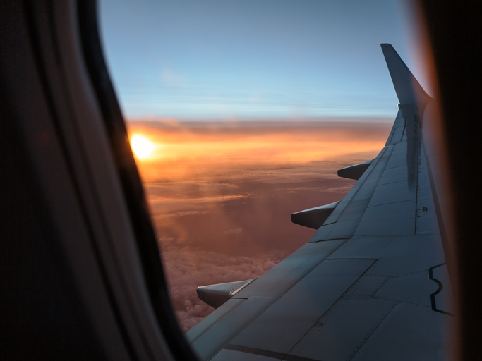 Looking Outside a Window of an Aircraft Cabin: White Airplane Wing and Sunset over the Clouds
