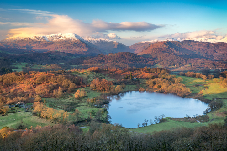 Taken from the top of Loughrigg Fell, a view down to Loughrigg Tarn in the Lake District UK, as early winter sunlight casts a golden red glow across the scene and the clouds, with snow topped fells in the distance.