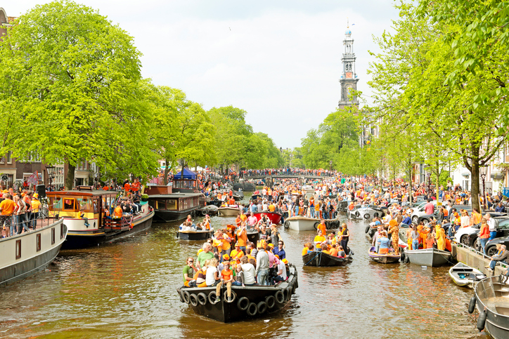 Amsterdam, The Netherlands - April 26, 2014: Amsterdam canals full of boats and people in orange at the Prinsengracht during the celebration of kings day on April 26, 2014 in Amsterdam, The Netherlands