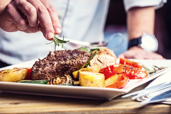 Chef in hotel or restaurant kitchen cooking only hands. Prepared beef steak with vegetable decoration.Chef in hotel or restaurant kitchen cooking only hands. Prepared beef steak with vegetable decoration.