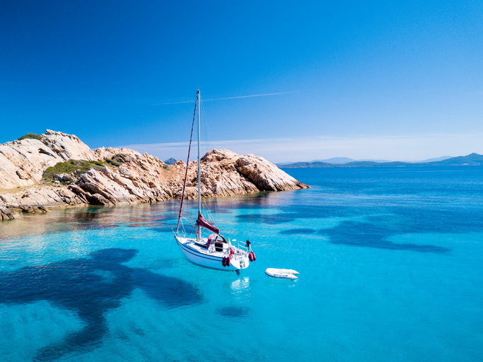"Aerial view of a sail boat in front of Mortorio island in Sardinia. Amazing beach with a turquoise and transparent sea. Emerald Coast, Sardinia, Italy.""t""n"
