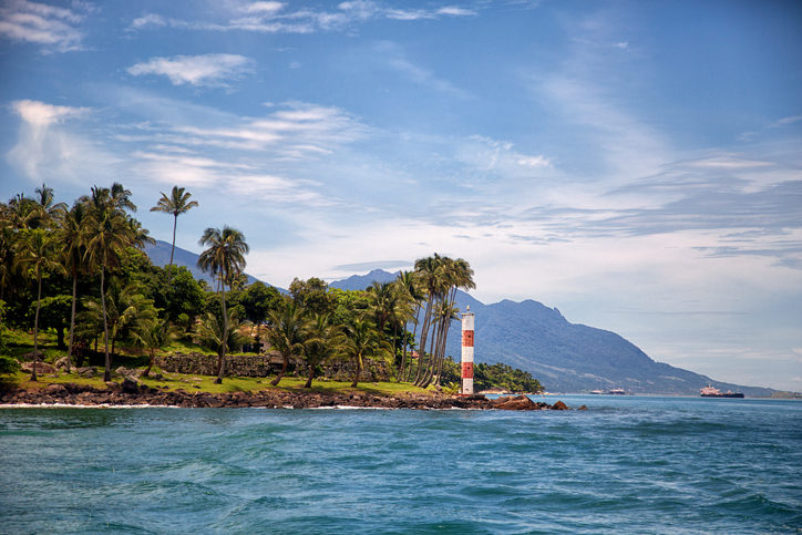 Coast of Ilhabela with clear blue water and a lighthouse
