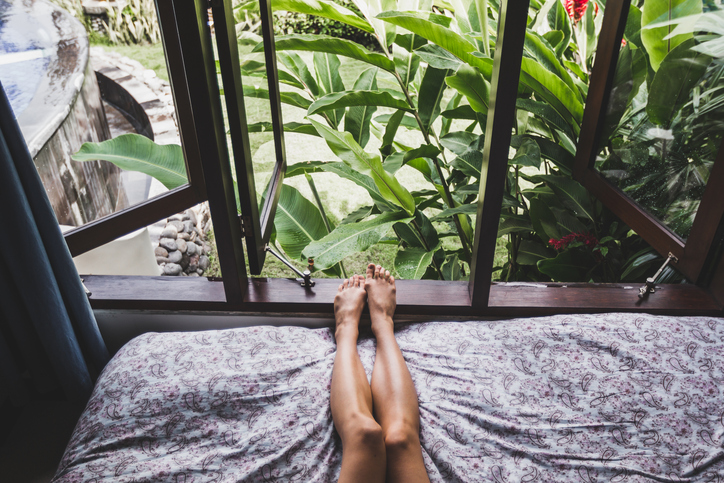 Woman legs in bed in the morning, view from window on tropical garden. Lifestyle photo