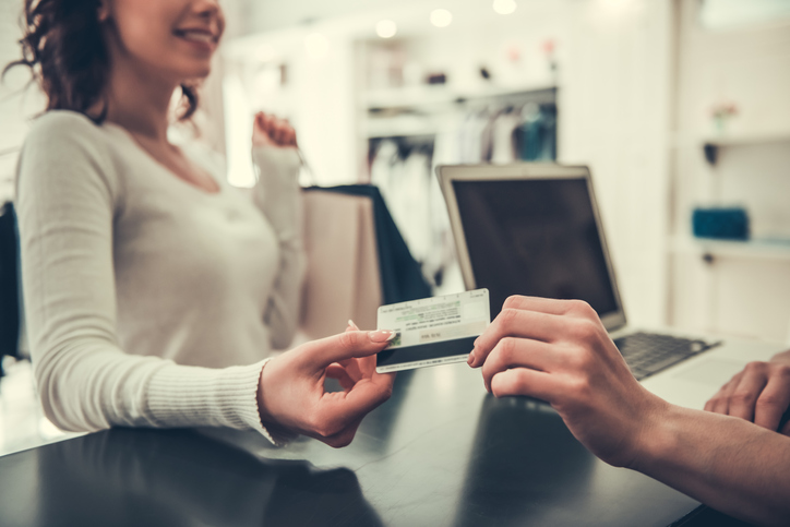 Attractive girl is giving a credit card to shop assistant and smiling while doing shopping in boutique