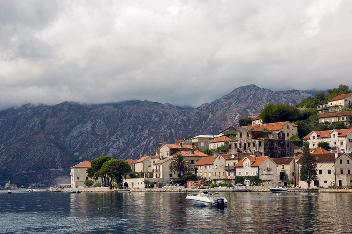 Perast, Montenegro - September 13: view on autumn Bay in the town of Perast, boat and Suzuki fire truck during the grape harvest festival on September 13, 2017