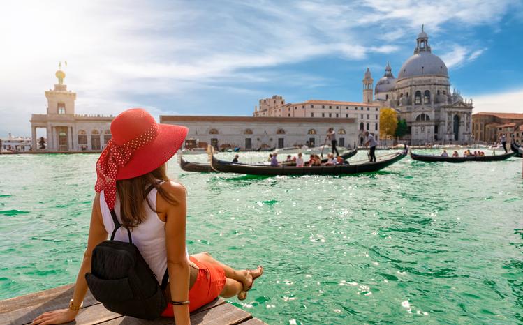 Attractive, female tourist enjoys the view to the Basilica di Santa Maria della Salute and Canale Grande in Venice, Italy