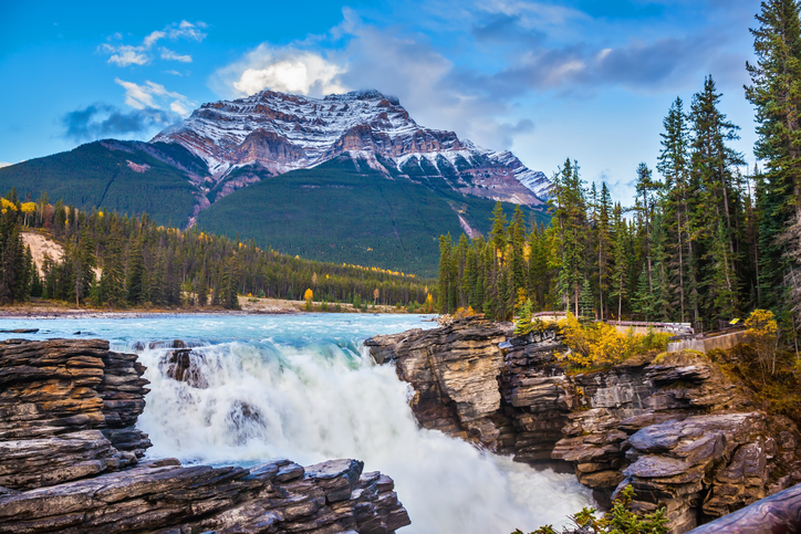 Powerful picturesque waterfall Athabasca. Pyramidal mountain covered with the first snow. Canada, Jasper National Park