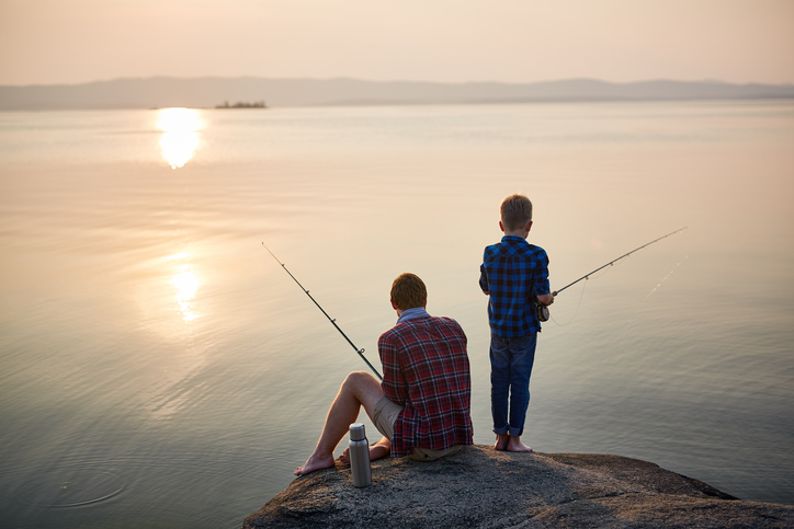Back view portrait of adult man and teenage boy sitting together on rocks fishing with rods in calm waters with landscape of setting sun, both wearing checkered shirts